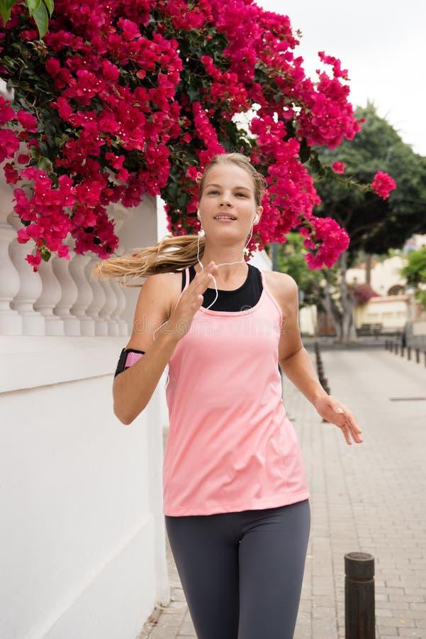 Mujer joven que sonríe como ella está corriendo foto de archivo libre de regalías