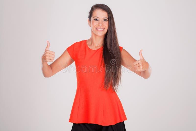 Mujer joven que sonríe con los pulgares para arriba foto de archivo