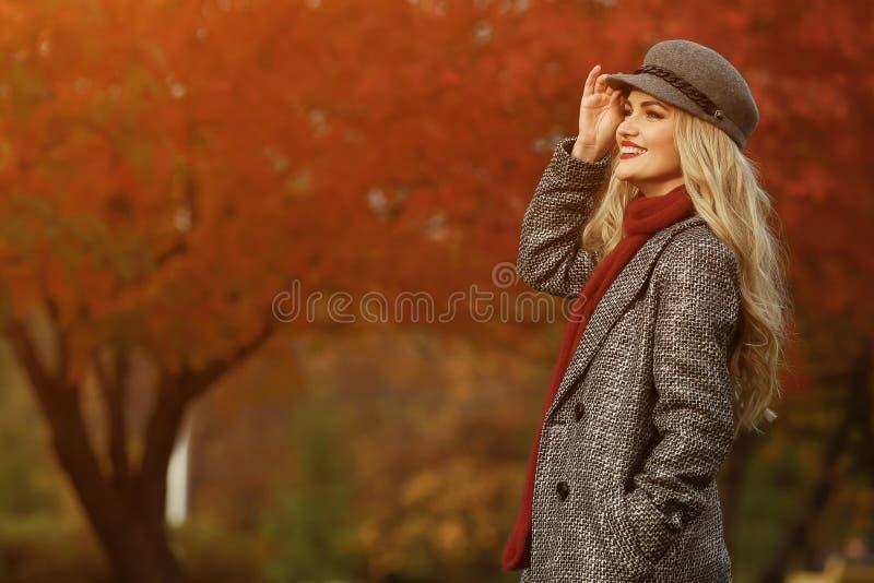 Mujer joven que sonríe en el fondo rojo del jardín imagen de archivo