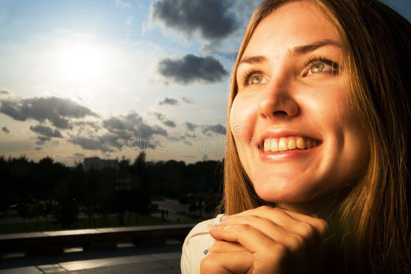 Mujer joven que sonríe en la puesta del sol foto de archivo libre de regalías