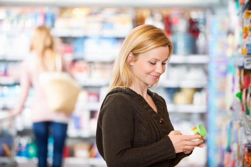 Mujer joven que sonríe mientras que hace compras fotografía de archivo