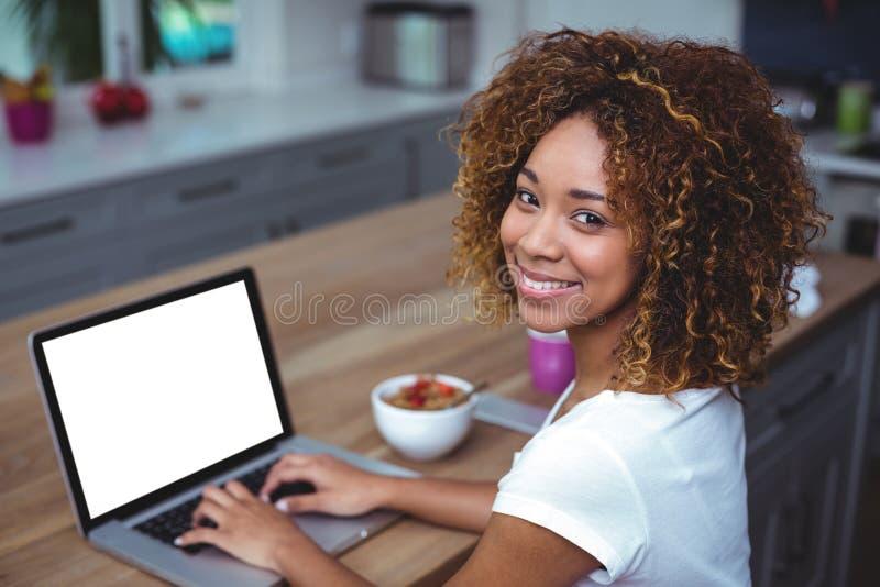 Mujer joven que sonríe mientras que usa el ordenador portátil en cocina imagen de archivo libre de regalías