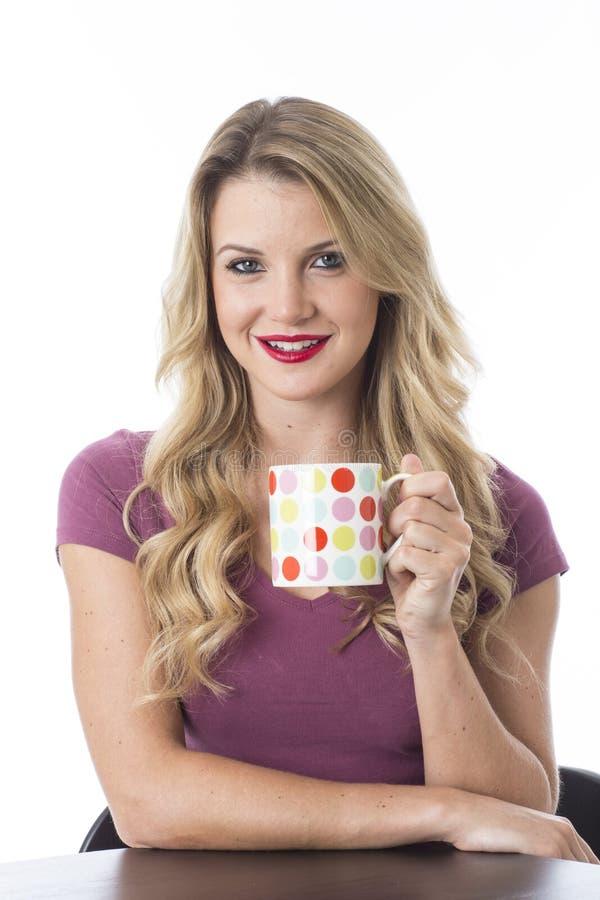 Mujer joven que sonríe sosteniendo la taza de café foto de archivo libre de regalías
