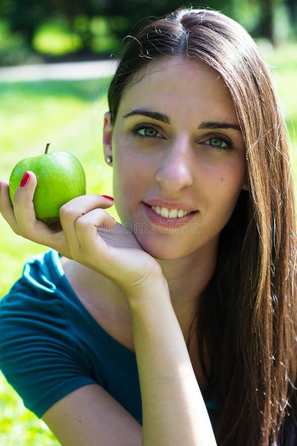 Mujer joven que sonríe sosteniendo una manzana foto de archivo libre de regalías