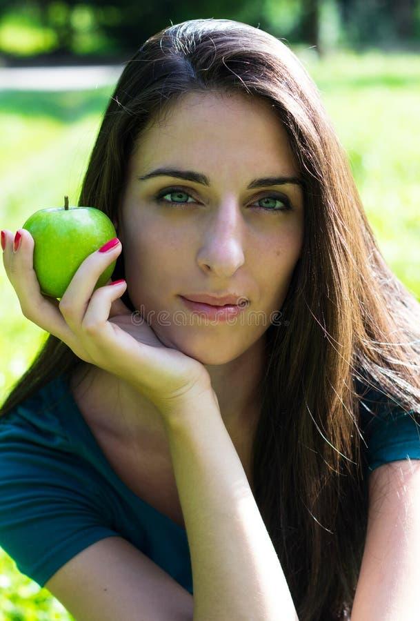Mujer joven que sonríe sosteniendo una manzana imágenes de archivo libres de regalías