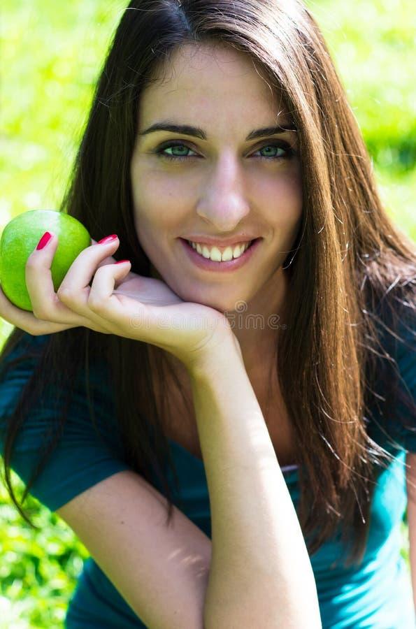 Mujer joven que sonríe sosteniendo una manzana foto de archivo