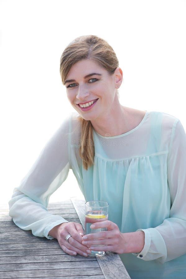 Mujer joven que sonríe y que disfruta de una bebida fresca en  imágenes de archivo libres de regalías