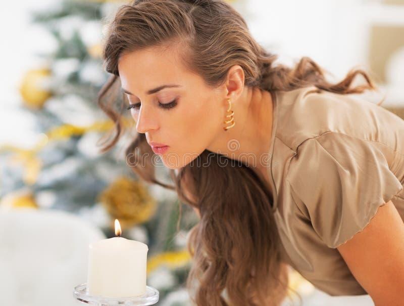 Mujer joven que sopla hacia fuera la vela delante del árbol de navidad foto de archivo