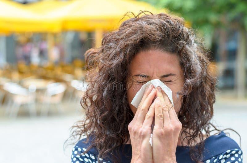 Mujer joven que sopla su nariz en un cuadrado urbano imagen de archivo libre de regalías