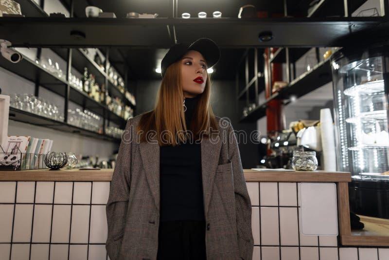 Mujer joven que sorprende en un casquillo negro elegante en una chaqueta gris del vintage en estilo retro con una nariz perforada fotos de archivo libres de regalías