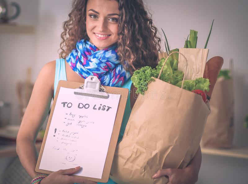 Mujer joven que sostiene el bolso de compras con las verduras Colocación en la cocina fotografía de archivo