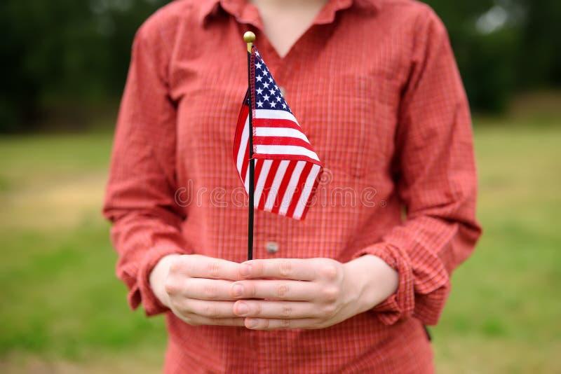 Mujer joven que sostiene el indicador americano Concepto del D?a de la Independencia imagen de archivo