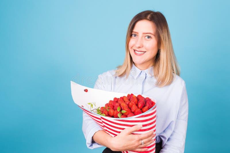 Mujer joven que sostiene el ramo de fresas en fondo azul fotografía de archivo libre de regalías