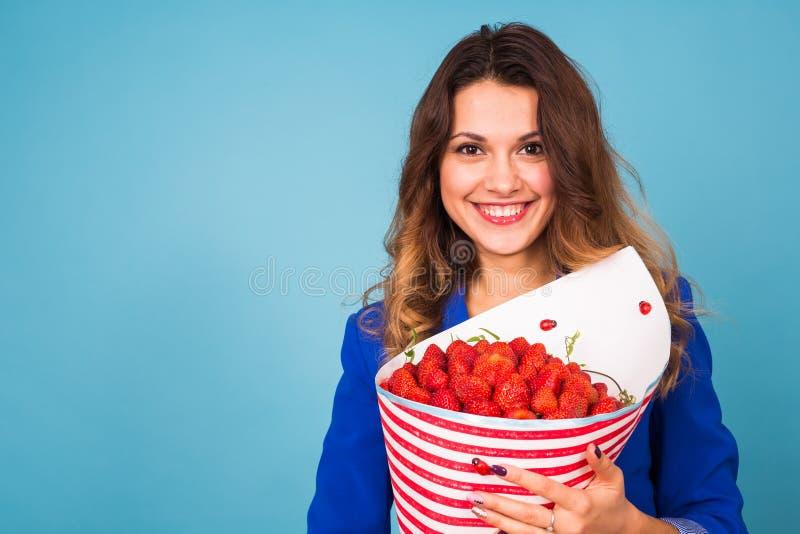 Mujer joven que sostiene el ramo de fresas en fondo azul fotografía de archivo