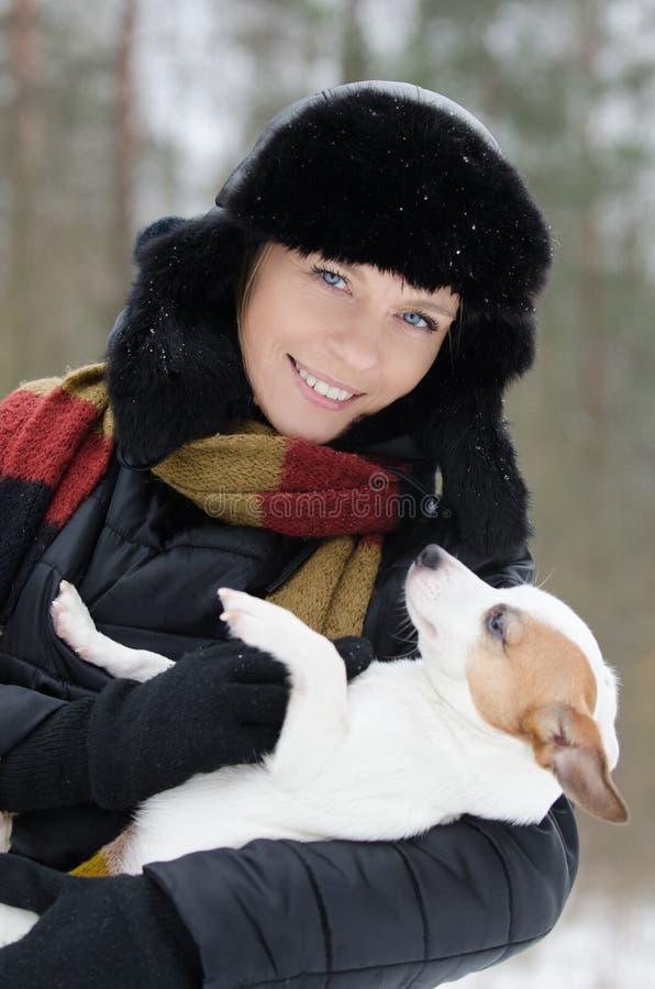 Mujer joven que sostiene el terrier de Jack Russell foto de archivo