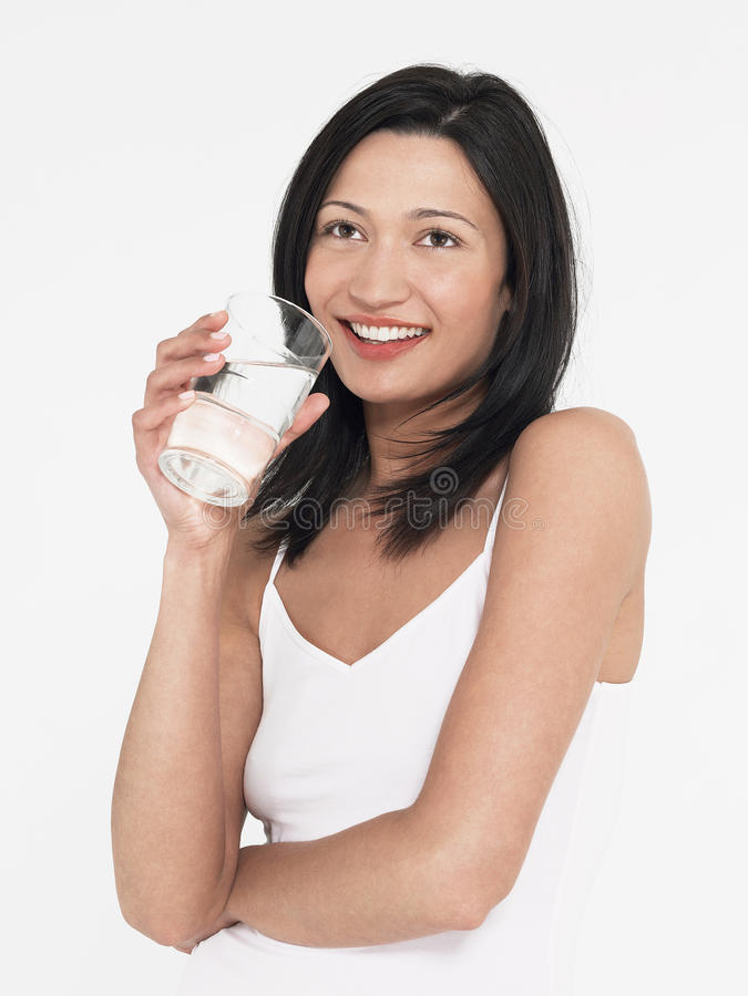 Mujer joven que sostiene el vidrio de agua imagen de archivo libre de regalías