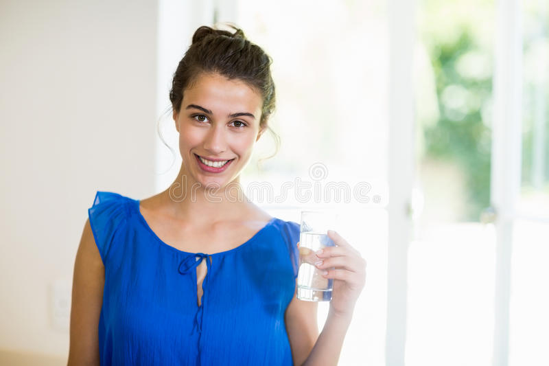 Mujer joven que sostiene el vidrio de un agua fotografía de archivo libre de regalías