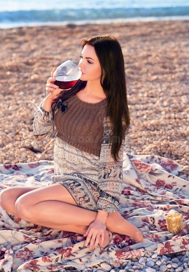 Mujer joven que sostiene el vidrio de vino italiano rojo Puesta del sol imagen de archivo libre de regalías