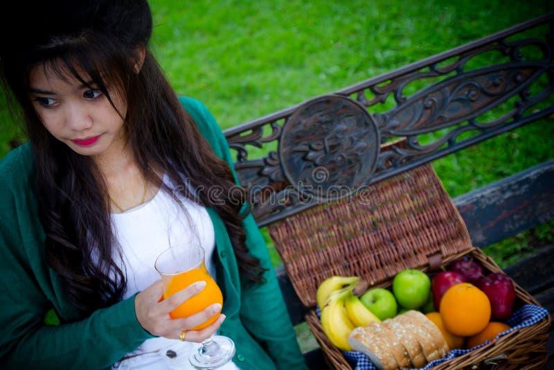 Mujer joven que sostiene el vidrio, zumo de naranja de consumición imagen de archivo libre de regalías