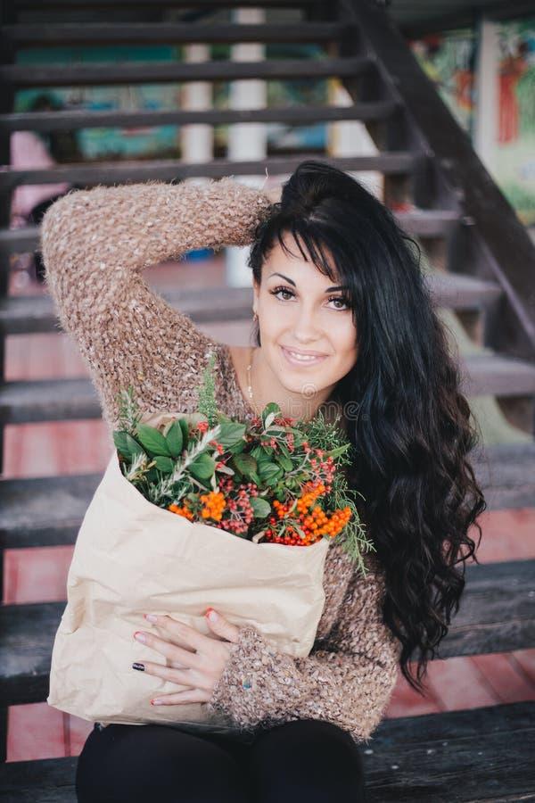 Mujer joven que sostiene la bolsa de papel con los ingredientes para la guirnalda de Navidad foto de archivo libre de regalías