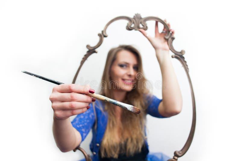 Mujer joven que sostiene la brocha y que alcanza hacia fuera de marco imagenes de archivo