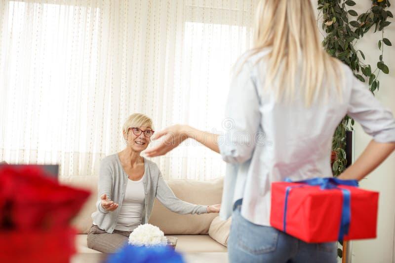 Mujer joven que sostiene la caja de regalo detrás de la parte posterior para su madre Sala de estar acogedora foto de archivo libre de regalías