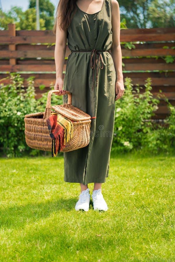 Mujer joven que sostiene la cesta de la comida campestre con la tela escocesa mientras que se coloca en césped verde imagen de archivo libre de regalías