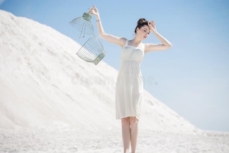 Mujer joven que sostiene la jaula de pájaros foto de archivo libre de regalías