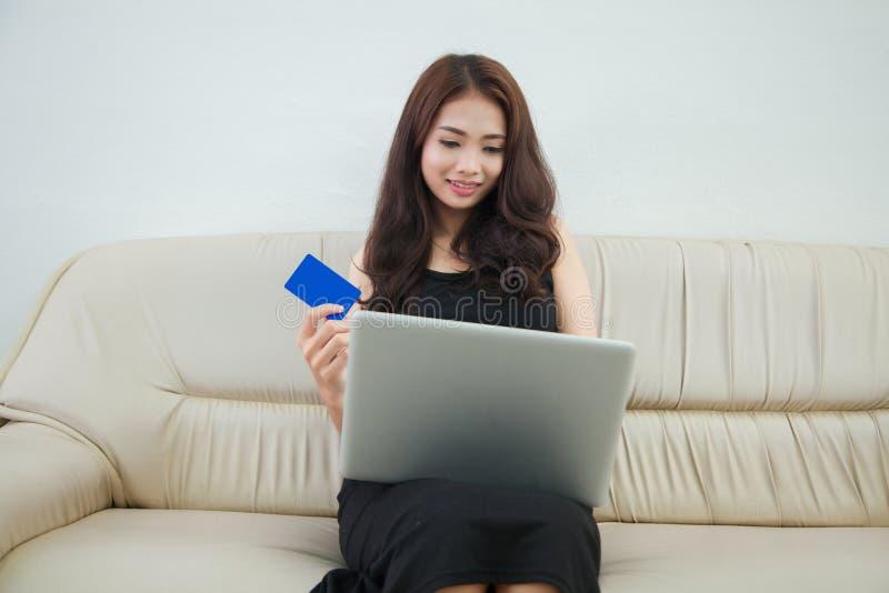 Mujer joven que sostiene la tarjeta de crédito y que usa el ordenador portátil Onlin imagenes de archivo