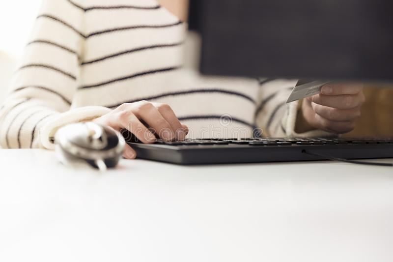 Mujer joven que sostiene la tarjeta de crédito y que usa el ordenador Shopp en línea imagen de archivo