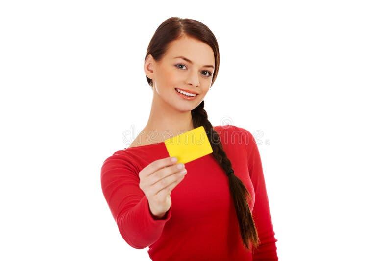 Mujer joven que sostiene la tarjeta de visita vacía imagenes de archivo