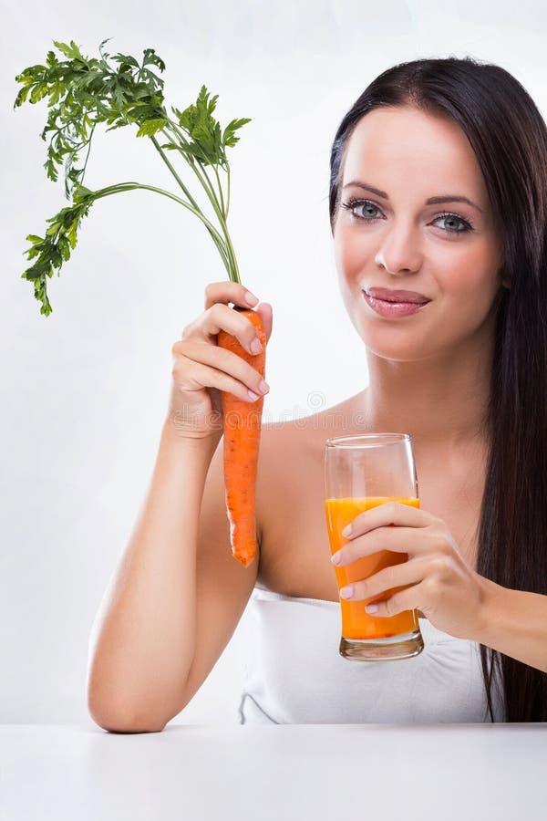 Mujer joven que sostiene la zanahoria y el jugo de zanahoria imagen de archivo