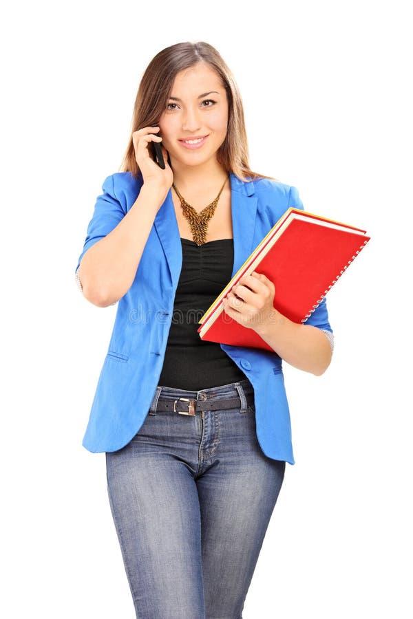 Mujer joven que sostiene los cuadernos y que habla en el teléfono celular fotos de archivo