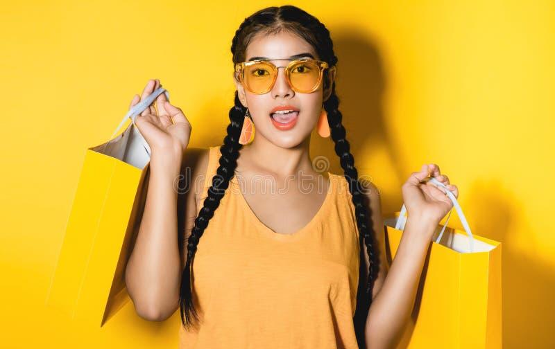 Mujer joven que sostiene muchos panieres en fondo amarillo imagenes de archivo