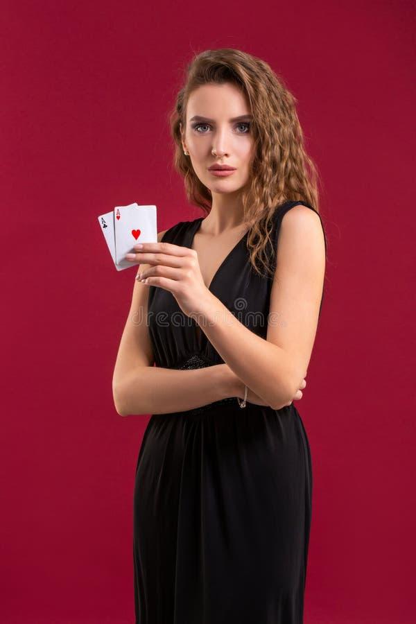 Mujer joven que sostiene naipes contra un fondo rojo Tiro del estudio foto de archivo