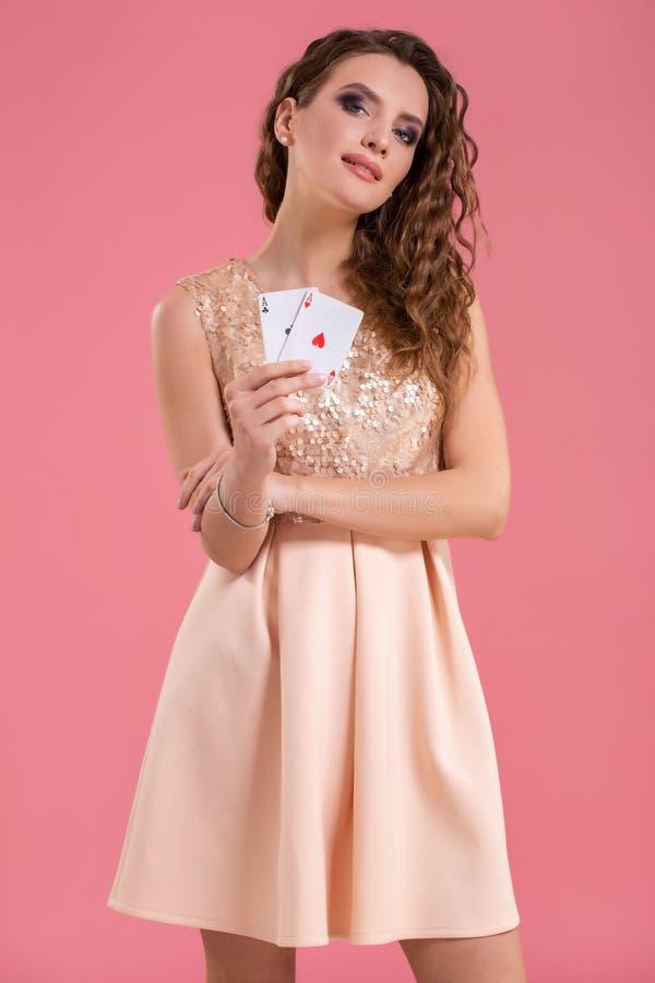 Mujer joven que sostiene naipes contra un fondo rosado Tiro del estudio fotos de archivo