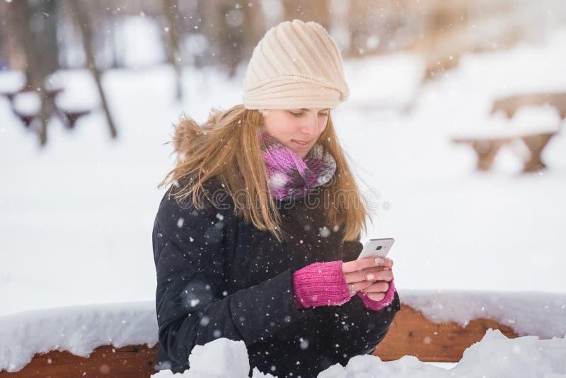 Mujer joven que sostiene smartphone en el parque durante día nevoso foto de archivo libre de regalías