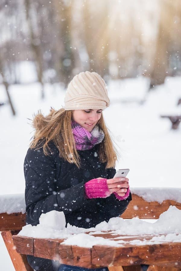 Mujer joven que sostiene smartphone en el parque durante día nevoso imágenes de archivo libres de regalías