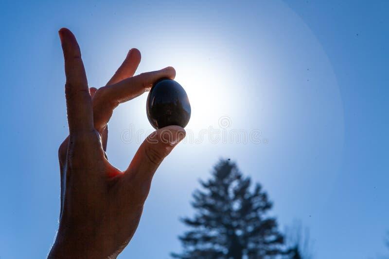 Mujer joven que sostiene su huevo sagrado del jade del yoni para arriba en el cielo fotografía de archivo libre de regalías