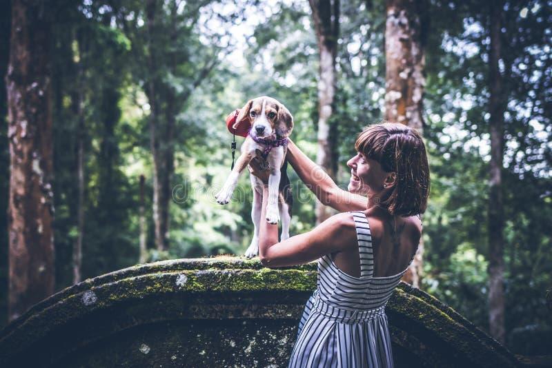Mujer joven que sostiene su perro del beagle del perrito en naturaleza de la isla tropical de Bali, Indonesia fotos de archivo libres de regalías