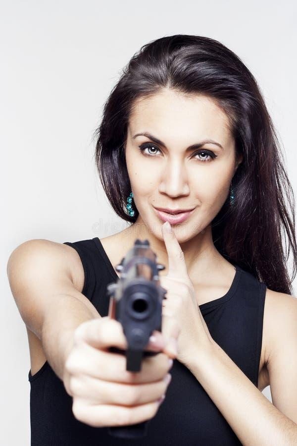 Mujer joven que sostiene un arma que dice shh imagen de archivo