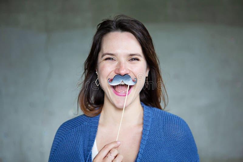 Mujer joven que sostiene un bigote falso a su cara imagenes de archivo