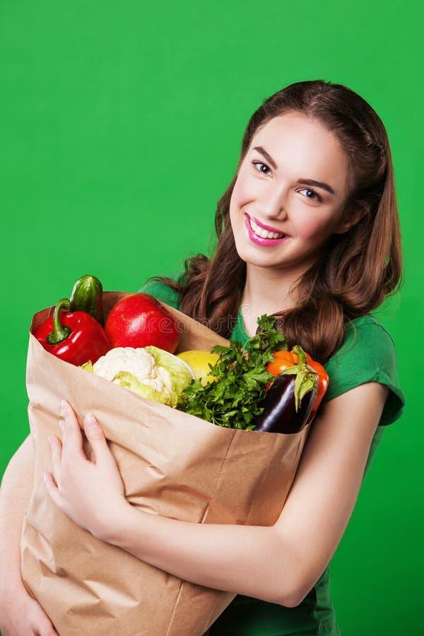 Mujer joven que sostiene un bolso lleno de comida sana imágenes de archivo libres de regalías