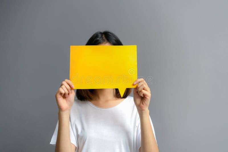 Mujer joven que sostiene un cartel en blanco para el texto en un fondo blanco fotos de archivo
