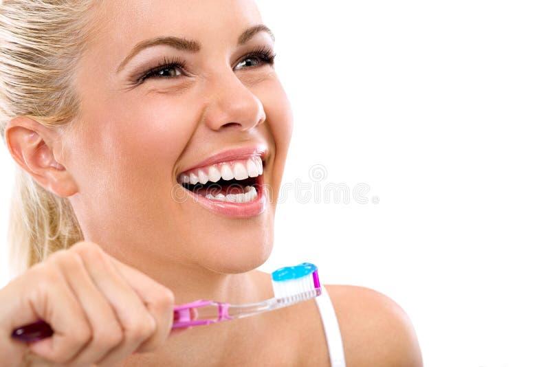 Mujer joven que sostiene un cepillo de dientes foto de archivo libre de regalías