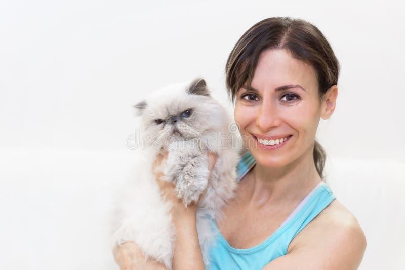 Mujer joven que sostiene un gato persa fotos de archivo libres de regalías
