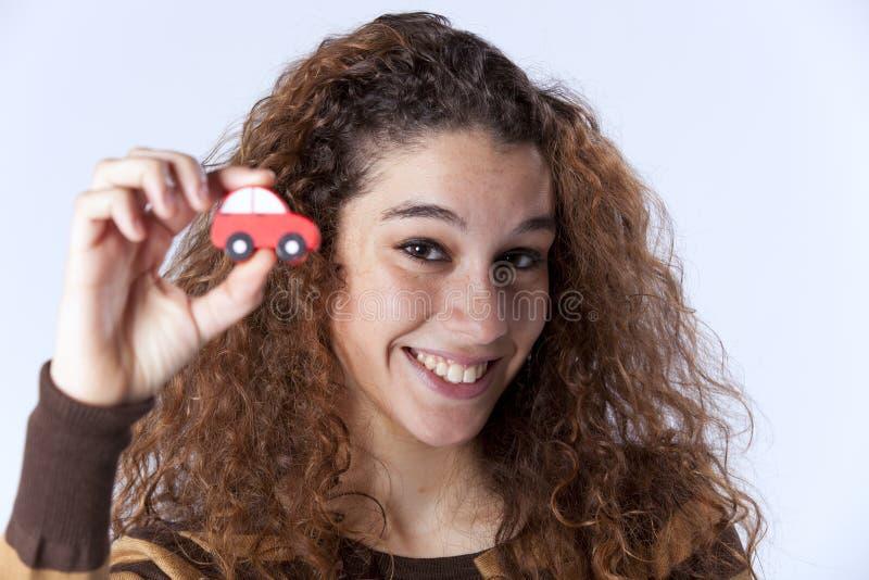 Mujer joven que sostiene un pequeño coche fotos de archivo libres de regalías