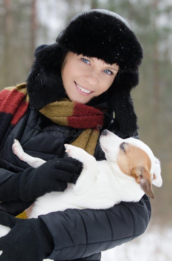 Mujer joven que sostiene un perro foto de archivo