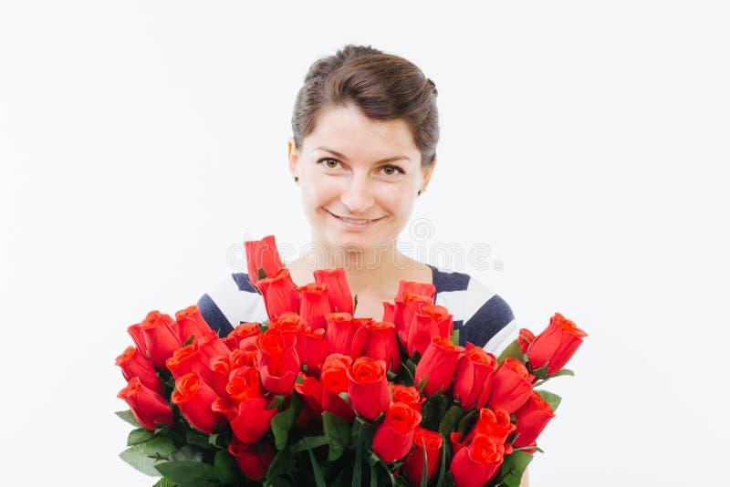 Mujer joven que sostiene un ramo de rosas imagen de archivo libre de regalías