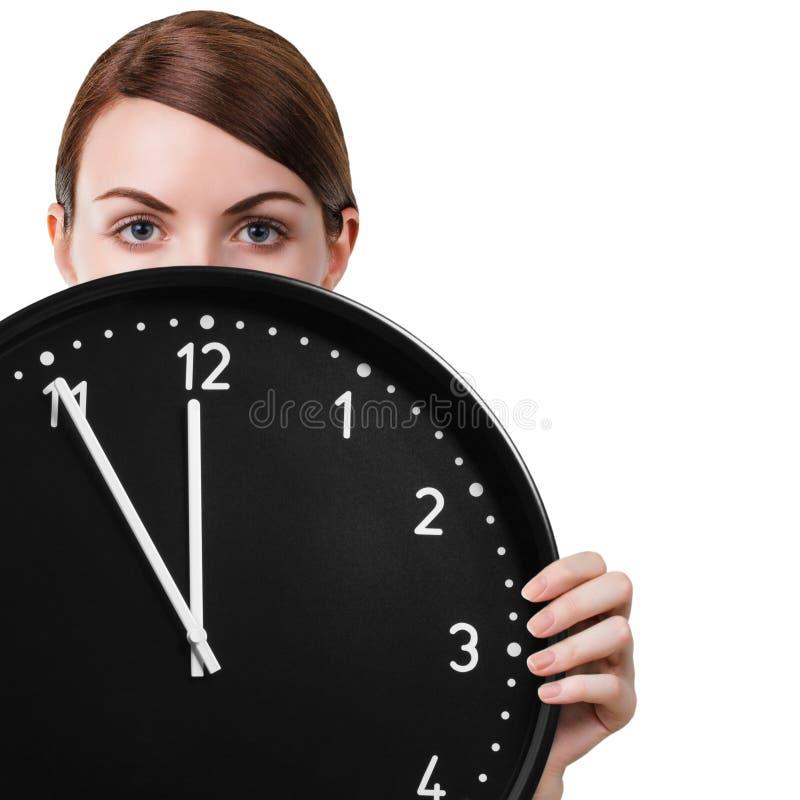 Mujer joven que sostiene un reloj fotografía de archivo libre de regalías